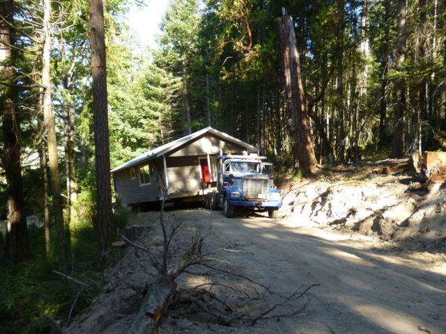 Belton Bros moving a house through the forest